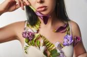 oříznutý pohled na dívku v podprsence s fialovými a fialovými květy na těle drží calla izolované na bílém