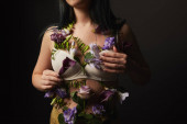 cropped view of girl in bra with violet and purple flowers on body isolated on black