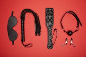 flat lay with various black sex toys isolated on red