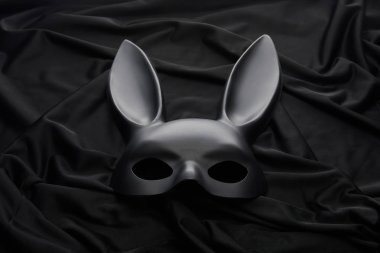 Rabbit mask on black textile background stock vector