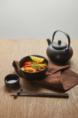 Photo noodles with shrimps and vegetables in bowl near chopsticks, soy sauce, teapot on napkin on wooden table isolated on grey