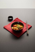 noodles with shrimps and vegetables in bowl near wooden chopsticks, soy sauce on red napkin on black background