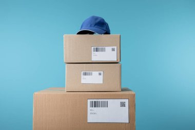 Cap on stacked cardboard boxes isolated on blue stock vector