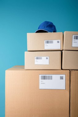 Cap on stacked cardboard boxes with qr and barecodes isolated on blue