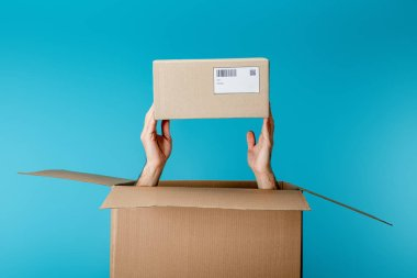Cropped view of courier holding cardboard box from package isolated on blue