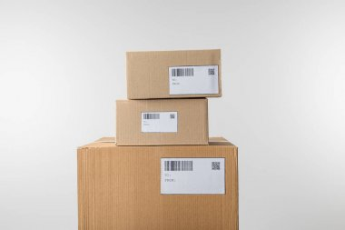 Stacked cardboard boxes with barcodes and qr codes on cards isolated on grey stock vector
