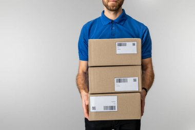 Cropped view of delivery man holding cardboard packages with qr codes and barcodes on cards isolated on grey