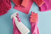 cropped view of housekeeper in pink rubber gloves holding sponge and spray bottle on blue with rags