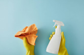 cropped view of housekeeper in yellow rubber gloves holding spray bottle and rag on blue