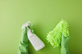 top view of housekeeper in rubber gloves holding spray bottle and rag on green