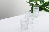 fasetované sklenice čerstvé vody na bílém stole v blízkosti zelené mírové lilie rostliny