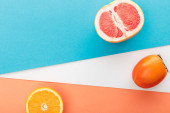 Photo Top view of grapefruit half, slice of citrus fruit and persimmon on blue, orange and white background