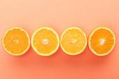 Horní pohled na řezané citrusové plody na oranžovém pozadí