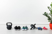 Photo sport shoes, skipping rope, abdominal wheel and kettlebell on floor at home