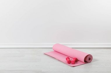 pink fitness mat and dumbbells on floor
