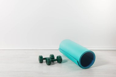 fitness mat and dumbbells on floor at home