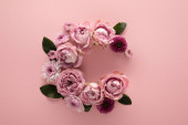 vrchní pohled na kvetoucí jarní květiny uspořádány jako písmeno C na růžovém pozadí