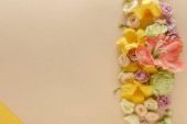 Photo top view of spring floral border on beige and yellow background