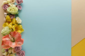 top view of spring floral border on beige, blue and yellow background