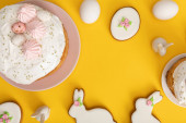 Top view of easter cakes with chicken eggs, cookies and decorative bunnies on yellow background