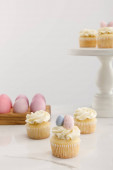 Delicious Easter cupcakes on surface and cake stand near painted chicken eggs on grey background