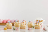 Delicious cupcakes with colorful painted chicken and quail eggs near easter cake isolated on grey