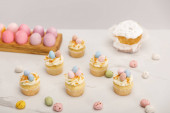 Cupcakes with painted chicken and quail eggs near traditional easter cake isolated on grey background