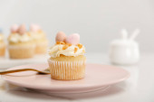 Photo Selective focus of cupcake on plate with fork on grey background
