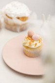 Selective focus of cupcake on plate and easter cake on white background