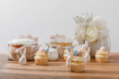 Selective focus of cupcakes with decorative bunnies, sugar bowl, easter cakes and vase with flowers isolated on grey