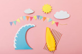 Top view of paper cut summer beach with surfboard and sunscreen on pink background