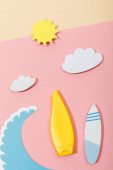 Top view of paper cut summer beach with tube of sunscreen on pink and beige