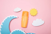 Top view of paper cut beach with dispenser bottle of sunscreen on pink background