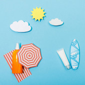 Top view of paper cut beach with bottle and tube of sunscreen on blue background