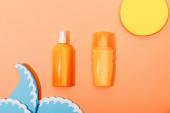 Horní pohled na dávkovač láhve opalovacího krému s papírem řezané slunce a mořské vlny na oranžovém pozadí