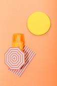 Draufsicht auf Papier geschnittene Sonne, Sonnenschirm und Decke mit Spenderflasche Sonnencreme auf Orange