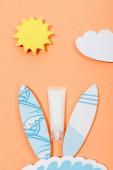 Draufsicht auf Papier geschnittene Sonne, Wolke, Meereswelle und Surfbretter mit Sonnenschutzrohr auf Orange