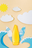 Top view of paper cut summer beach with tube of sunscreen on beige background