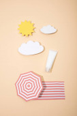 Top view of paper cut sun, clouds, beach umbrella and blanket with tube of sunscreen on beige