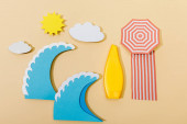 Photo Top view of paper cut summer beach with tube of sunscreen on beige background