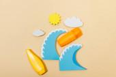 Draufsicht auf Papier geschnittene Sonne, Wolken, Meereswellen mit Röhre und Flasche Sonnencreme auf Beige