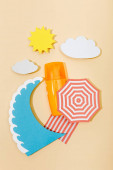 Top view of paper cut summer beach with sea wave and bottle of sunscreen on beige