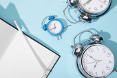 Photo top view of classic alarm clocks with blank netbook and pencil on blue background