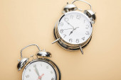 Photo top view of classic alarm clocks on beige background