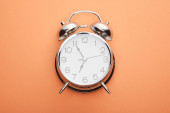 Photo top view of classic alarm clock on peach background