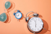 Photo top view of alarm clocks and hourglass on peach background