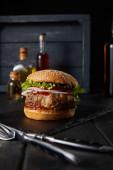 selektivní zaměření hamburgru na tmavé sekací prkno u vidlice, nůž, olej a ocet láhve izolované na černé