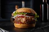 selektivní zaměření chutného burgeru na tmavý povrch, pivo, ocet a olejové láhve izolované na černém