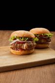 dva chutné hamburgery na dřevěné řezací desce izolované na černé