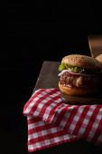 burger na dřevěné řezací desce na kostkovaném ubrusu izolované na černé